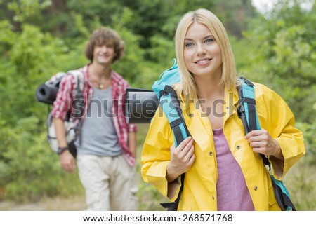 Smiling female backpacker looking away with man standing in background at forest - stock photo