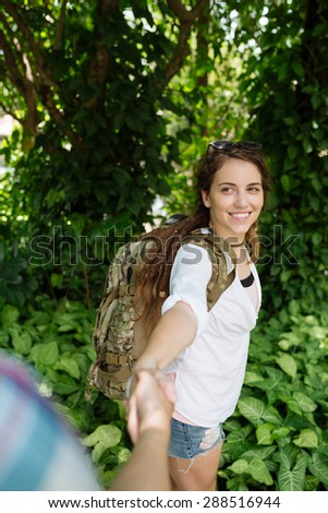 Smiling female backpacker taking helping hand of her boyfriend