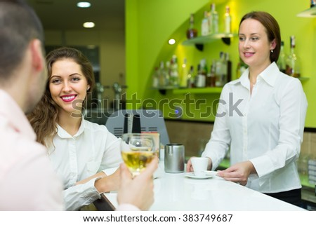 Smiling female barista and two clients at counter in small bar. Focus on girl