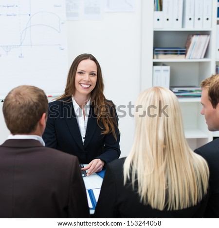 Smiling female boss or team leader sitting at a table facing her team of diverse business professionals who are seated with their backs to the camera - stock photo