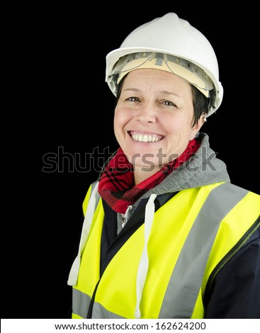 smiling female builder / construction worker wearing helmet and high visibility vest - stock photo