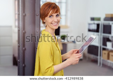 Smiling female business owner leans against beam and checks inventory in the store room - stock photo