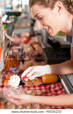Smiling female butcher packing delicious meal at shop
