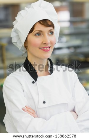 Smiling female chef posing in a kitchen looking away - stock photo