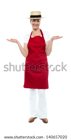 Smiling female chef with warm welcome gesture - stock photo