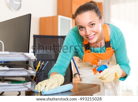 Smiling female cleaner in uniform making cleaning in the office-room