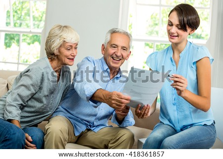 Smiling female consultant showing report to senior couple at home