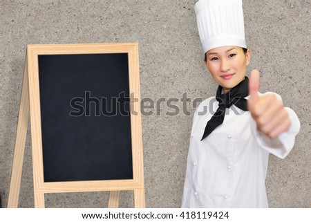 Smiling female cook gesturing thumbs up in kitchen against path