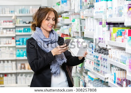 Smiling female customer scanning product through cell phone in pharmacy - stock photo