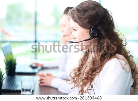Smiling female customer service representative talking on headset with colleagues in background at office - stock photo