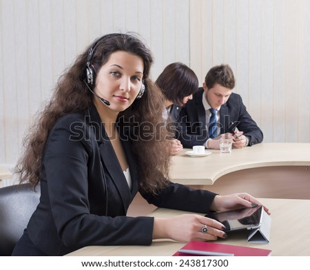 Smiling female customer support officer. Portrait of smiling cheerful customer support phone operator in headset with her co-workers on the background - stock photo