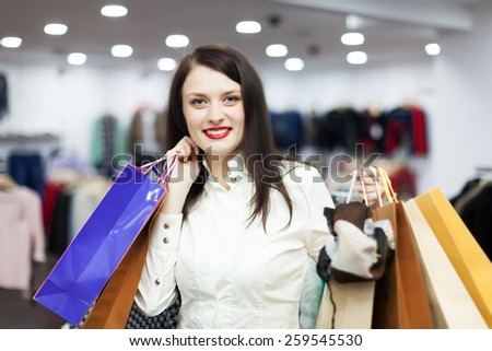 Smiling female customer with shopping bags at clothing boutique - stock photo