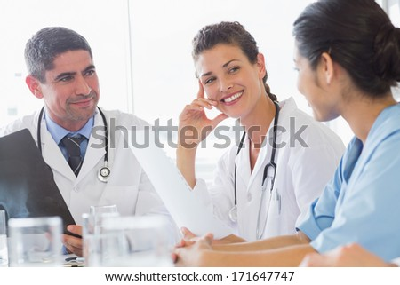 Smiling female doctor discussing with nurse and colleague in hospital