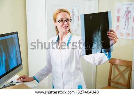 Smiling female doctor in glasses looking at x-ray at office and working at the computer  - stock photo
