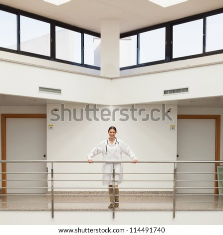 Smiling female doctor leaning on the railing in hospital stairwell - stock photo