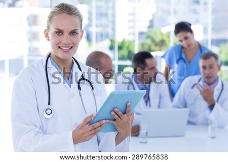 Smiling female doctor looking at clipboard while her colleagues works lo - stock photo