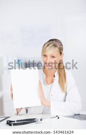 Smiling female doctor sitting and showing blank paper - stock photo
