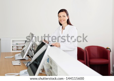 Smiling female doctor standing at the reception desk - stock photo