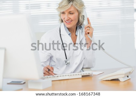 Smiling female doctor with computer using phone at medical office - stock photo