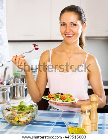 Smiling female eating healthy salad with corn and herbs