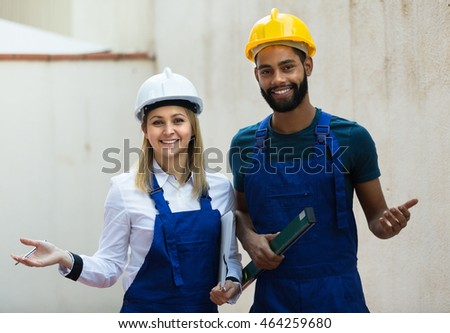 Smiling female engineer and black specialist making wall plane
