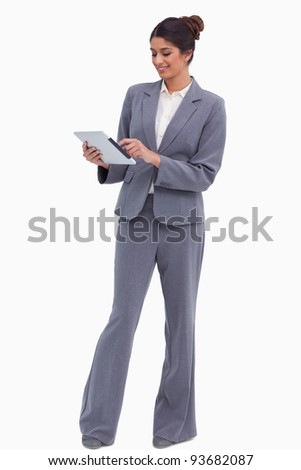 Smiling female entrepreneur working on her tablet computer against a white background