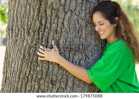 Smiling female environmentalist hugging tree trunk in park - stock photo