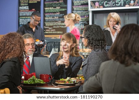 Smiling female executive eating lunch with coworkers - stock photo