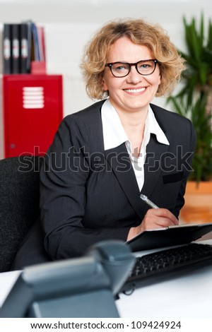 Smiling female executive writing notes on clipboard looking at you - stock photo