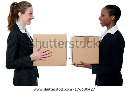 Smiling female executives holding cardboard boxes