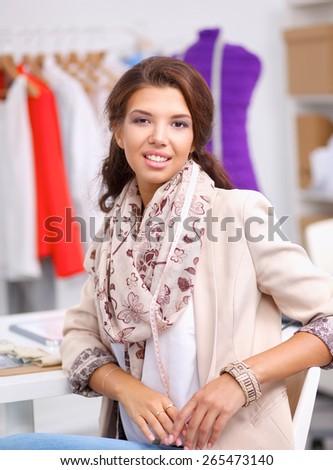 Smiling female fashion designer sitting at office desk - stock photo