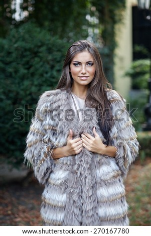 Smiling female fashion model posing in a fur coat outdoor - stock photo