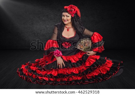 Smiling female flamenco dancer sits half-turned on a stage floor. The mature woman wears red and black flamenco floor-length gown with frills. She holds a fan with left hand and looks at camera.