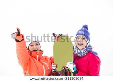 Smiling female friends with snowboard outdoors - stock photo