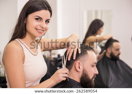 Smiling female hairdresser is cutting hair of man client. - stock photo