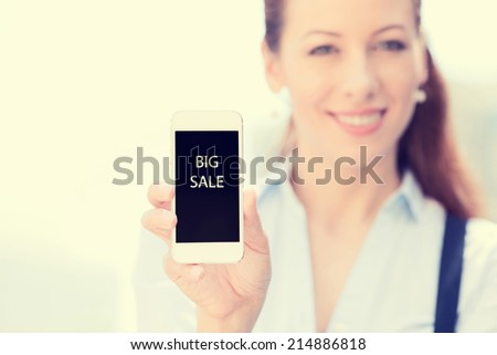 Smiling female holding mobile smart phone with big sale sign on screen, isolated outside city background, focus on smartphone. Advertisement concept. Positive human emotions, new technology event - stock photo