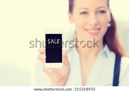 Smiling female holding mobile smart phone with sale sign on screen, isolated outside city background, focus on smartphone. Advertisement concept. Positive human emotions, new technology event - stock photo