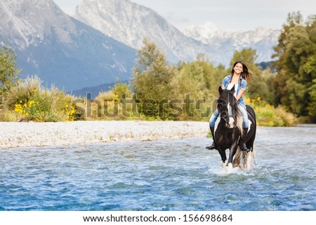 Smiling Female horse rider crossing river in a mountainous landscape