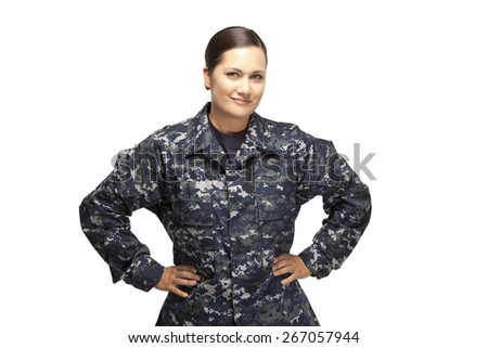 Smiling female in navy uniform posing with hands on hips against white background - stock photo