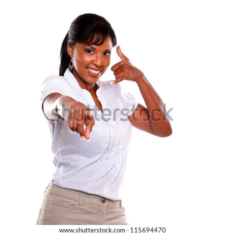 Smiling female looking and pointing at you saying call me on isolated background - stock photo