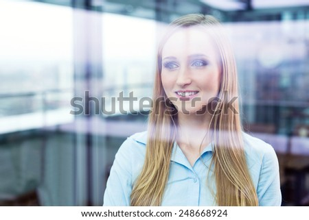 Smiling female manager standing in an office and looking through a window - stock photo
