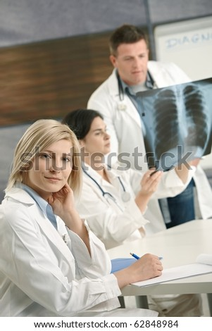 Smiling female medical doctor looking at camera, doctors consulting diagnosis of x-ray image in background.?
