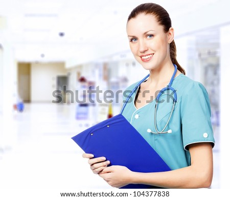 Smiling female medical doctor with clipboard in a corridor of a hospital - stock photo