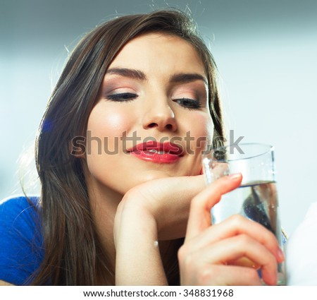 Smiling female model portrait with water glass. Beautiful girl. Young woman drink water.