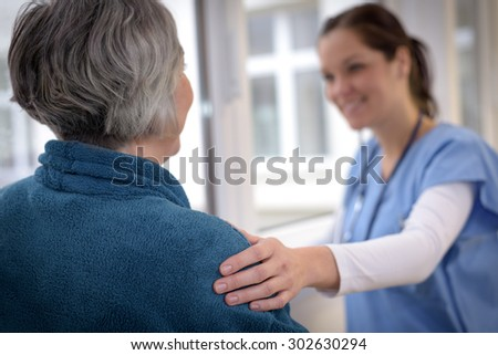Smiling female nurse comforting senior patient in hospital corridor - stock photo