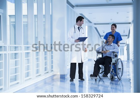 Smiling female nurse pushing and assisting patient in a wheelchair - stock photo