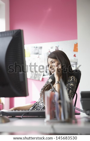 Smiling female office worker using phone at office desk - stock photo