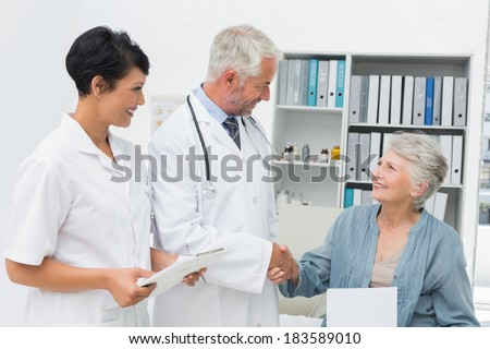 Smiling female patient and doctor shaking hands in the medical office - stock photo