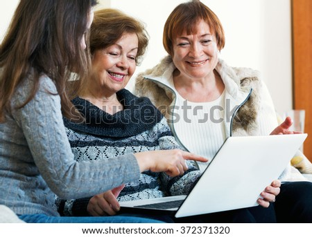 Smiling female pensioners and young cute relative browsing web on laptop  - stock photo