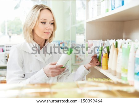 Smiling female pharmacist woman working in pharmacy drugstore - stock photo
